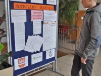 Zdjęcie przedstawiające ucznia przed tablicą informacyjną w szkole