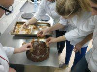 Zdjęcie przedstawiające uczniów dekorujących ciasto