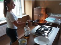 Zdjęcie przedstawiające uczennicę w trakcie zajęć kulinarnych