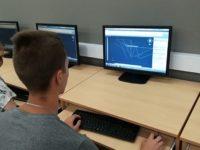 Zdjęcie przedstawiające ucznia w czasie zajęć informatycznych