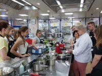 Zdjęcie przedstawiające uczniów i kucharza w trakcie warsztatów kulinarnych