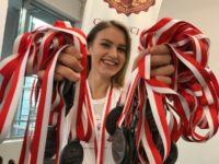 Zdjęcie przedstawiające dziewczynę trzymającą w rękach medale