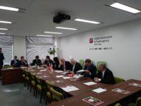 Zdjęcie przedstawiające ludzi siedzących przy stole konferencyjnym