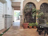 Zdjęcie przedstawiające podwórko z krzesłami, stolikiem i roślinami
