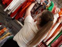 Zdjęcie przedstawiające młodą kobietę w sklepie odzieżowym